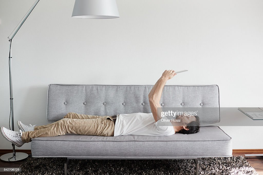 Relaxed man lying on couch holding digital tablet