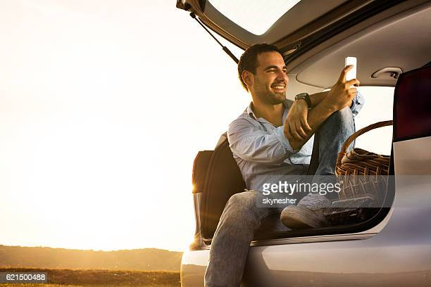 Relaxed man using smart phone in car trunk at sunset.