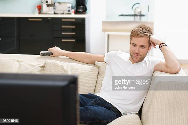 relaxed man watching television smiles contentedly