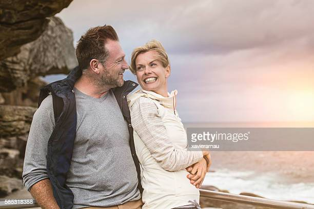 Relaxed mature couple next to the sea watching sunrise