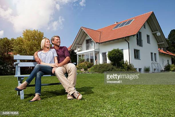 Relaxed mature couple sitting on bench in garden