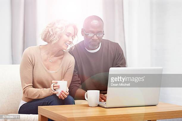 Relaxed mature couple using laptop at home