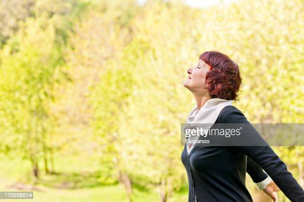 Relaxed Mature Woman Enjoying Freedom of Nature in Spring