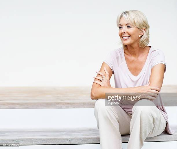 Relaxed mature woman sitting on staircase while looking away