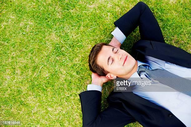 ゆったりした 30 代のビジネスの男性芝生のベッドでぐっすりとお休みいただけます。