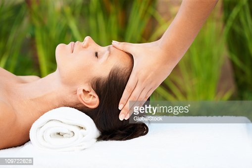 Relaxed mid adult woman receiving head massage : Stock Photo