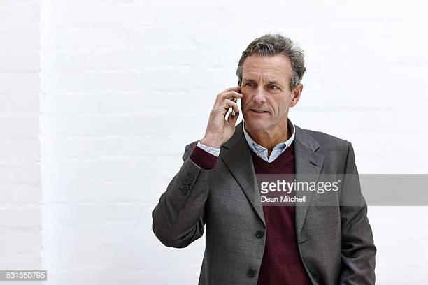 ゆったりした中央歳のビジネスマンが携帯電話で話している