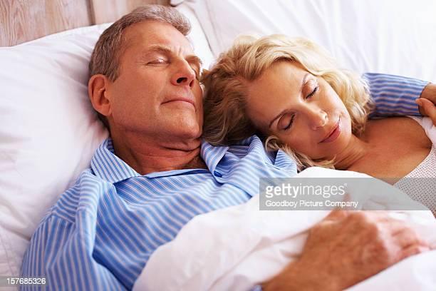 Rilassato medio invecchiato donna dormire accanto a uomo maturo