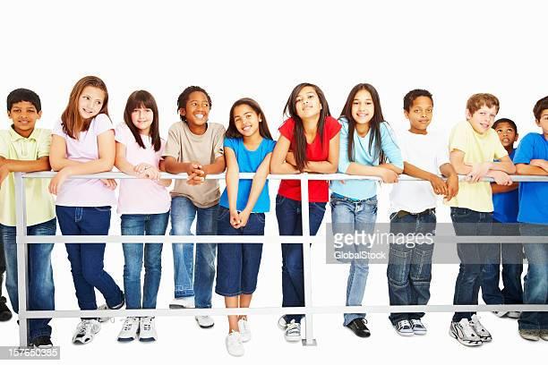 Descontraído multi étnica crianças a inclinar-se na Vedação de Corrimão