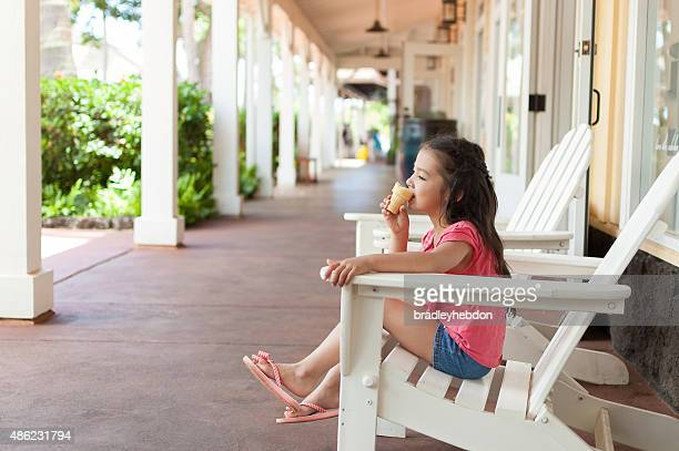 Relaxed pretty little girl eating an ice-cream cone
