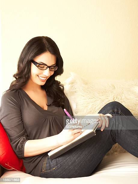 Relaxed pretty young woman writing in journal on sofa