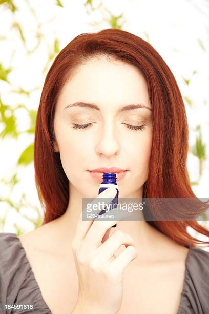 Relaxed redhead woman smelling essential oil with eyes closed