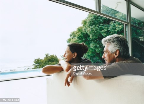 Relaxed Senior Couple Sitting in Their Home on the Coast Looking Out of the Window : Stock Photo