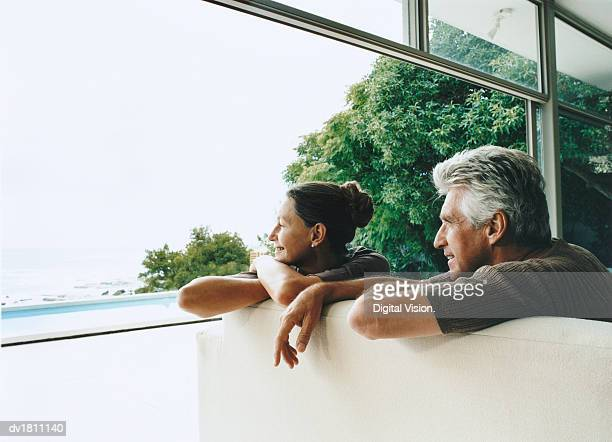 Relaxed Senior Couple Sitting in Their Home on the Coast Looking Out of the Window