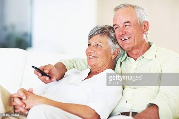 Entspannte altes Paar beobachten Fernseher