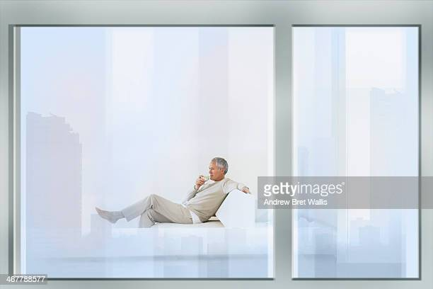 Relaxed senior man drinking water in apartment