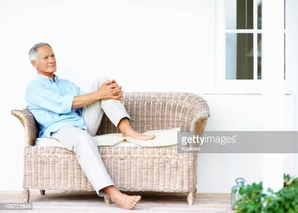 Détente senior homme assis sur un canapé Regarder ailleurs