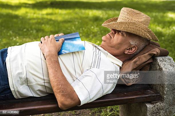 Relaxed senior man taking a nap on a bench outdoors.