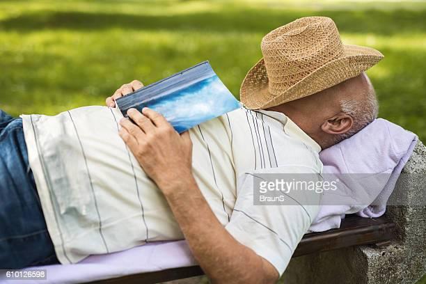 Lässig Alter Mann ein Nickerchen auf einer Bank im Freien.
