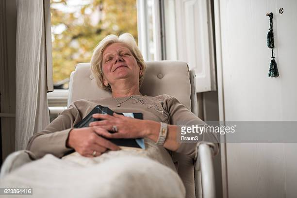 Relaxed senior woman fell asleep after reading a book.