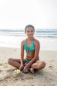 Smiling teenage girl sitting on a sand at the beach and looking at the camera.