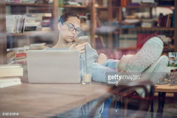 Relaxed teenage student using mobile phone in the library.