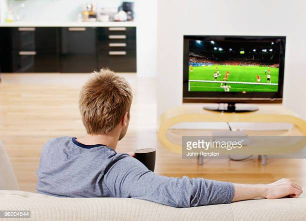 relaxed watching football on settee on television