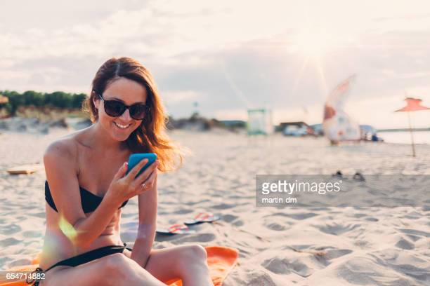 Relaxed woman at the beach texting