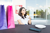 Relaxed beautiful woman drinking coffee with shopping bags on table in mall