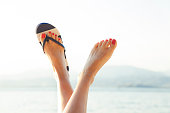 Young girl feet in colorful flipflop sandal on sea beach