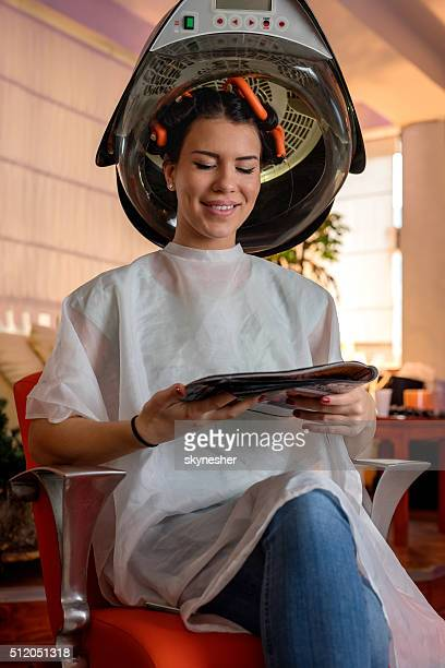 Relaxed woman in hair salon reading magazine under hair dryer.