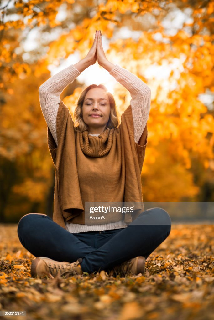 Relaxed woman meditating in autumn day at the park. : Stock-Foto