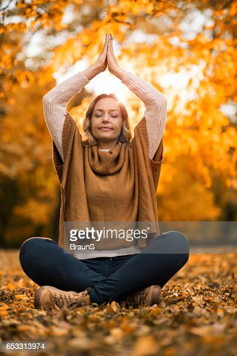 Relaxed woman meditating in autumn day at the park. : Stock Photo