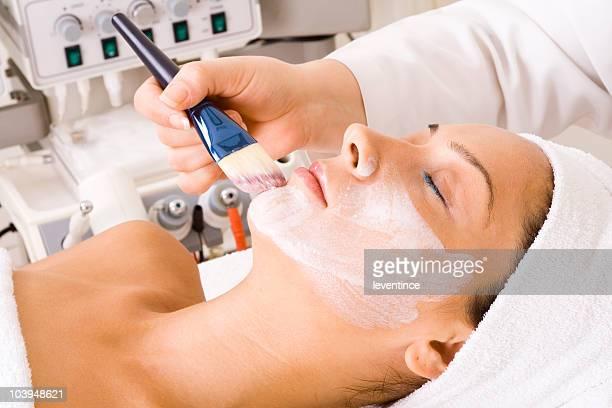 A relaxed woman receiving a facial mask