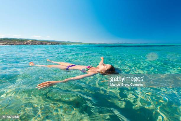 Relaxed woman stays afloat at sea