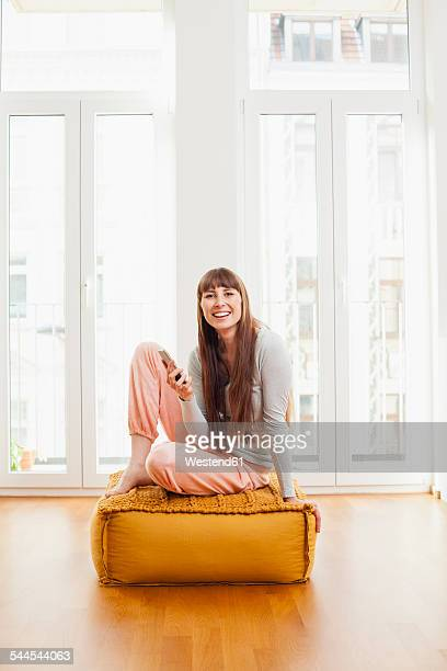 Relaxed woman with cell phone on ottoman at home