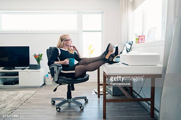 Relaxed woman working from home office, full length with copyspace.