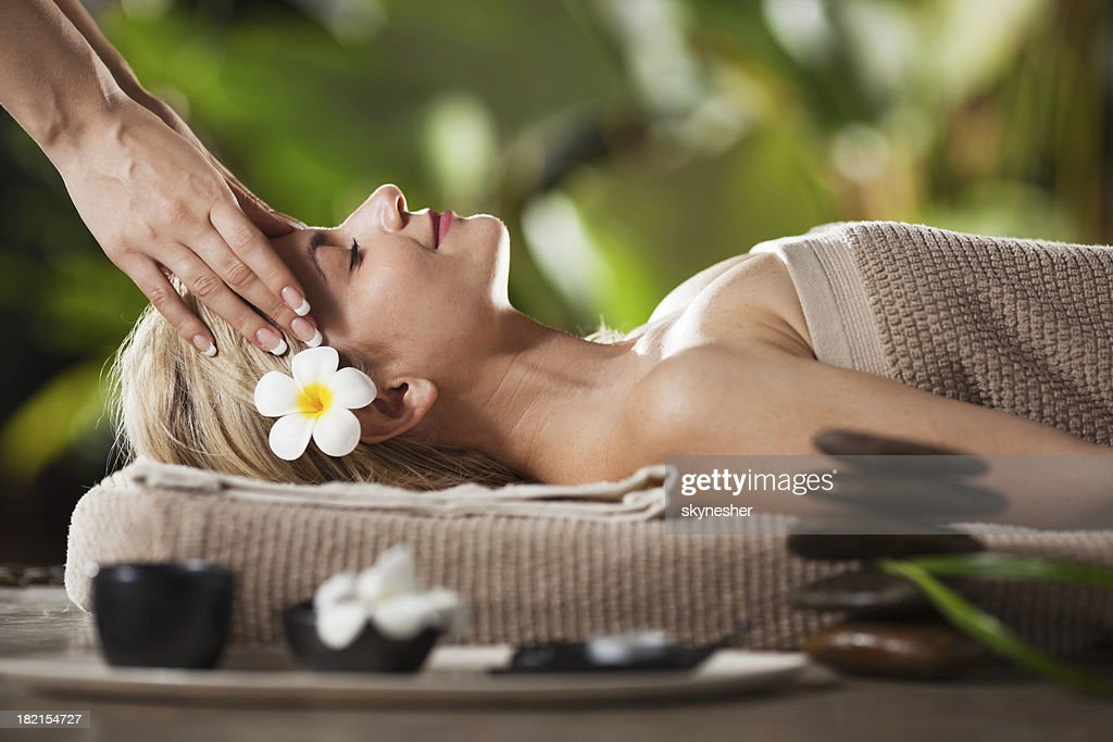 Relaxed young adult woman receiving head massage.