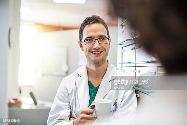 Détendue jeune mâle pharmaciens avec une tasse de café