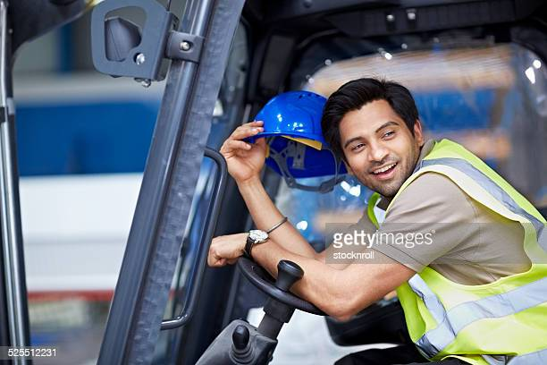Relaxed young man sitting in a forklift truck at warehouse