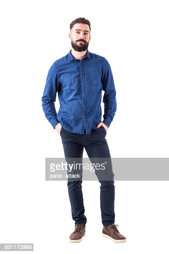 Relaxed young man wearing blue denim shirt with hands in pockets looking at camera : Stock Photo