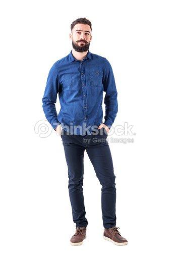 편안 하 게 젊은 남자와 블루 데님 셔츠를 입고 카메라를 보고 주머니에 손을 : 스톡 사진