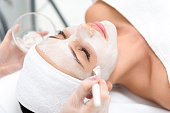 Close up of female face getting healthy clay mask by beautician