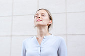 Relaxed young woman feeling spiritual energy while meditating outdoors. Serene beautiful woman with closed eyes breathing of fresh air. Balance concept