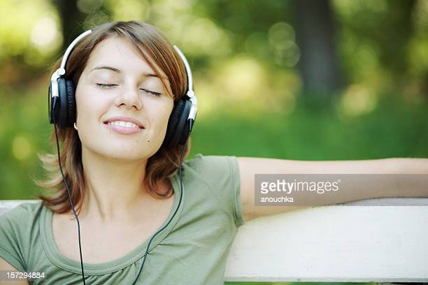 Relaxed young woman listening music in park
