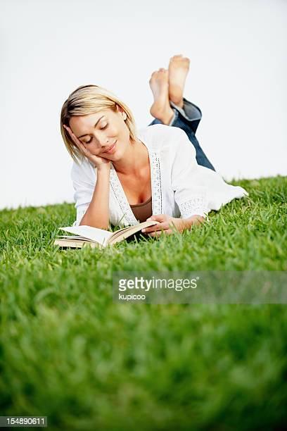 Rilassato e giovane donna lettura libro sull'erba verde
