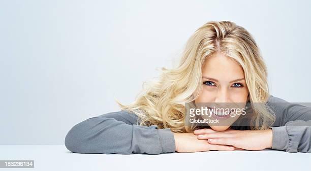 Entspannte Junge Frau lächelnd vor weißem Hintergrund