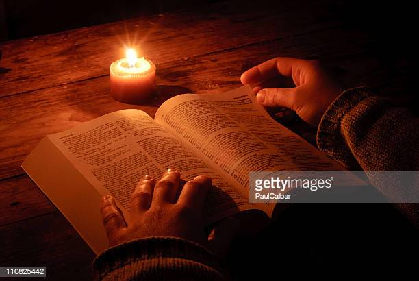 Relaxing and reading bible by candlelight at night