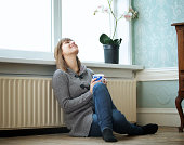 Portrait of a happy young woman sitting on the floor and leaning against radiator. Smiling female looking up and relaxing at home.