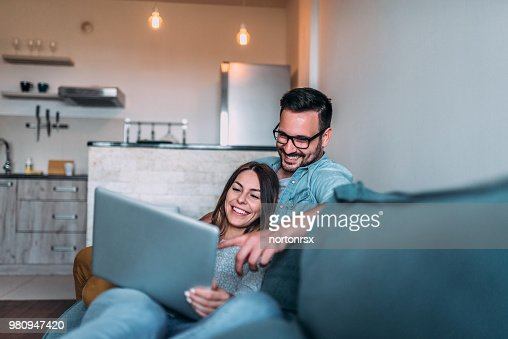 Relaxing at home, watching photos on laptop. : Stock Photo